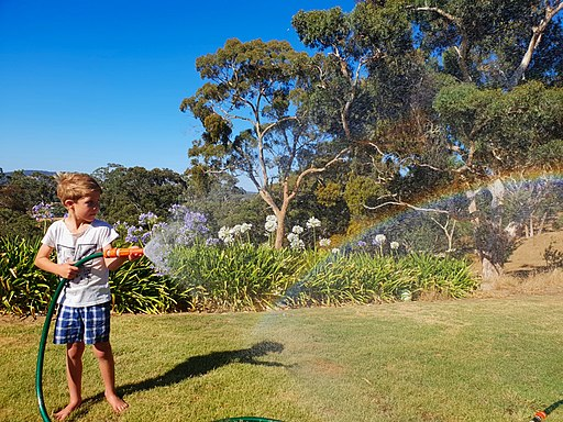 Boy making a rainbow with a garden hose